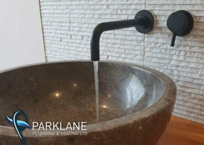 Stone carved basin with wall mounted Cifial matte black taps.