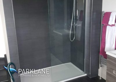 Low profile shower tray with single glass panel.
